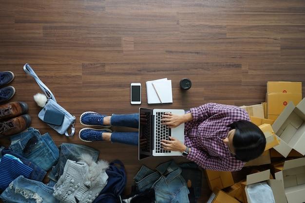 Vue de dessus du propriétaire d'une petite entreprise travaillant sur un ordinateur portable
