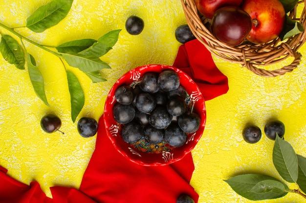 Vue de dessus du prunellier frais avec des prunes sur la surface jaune