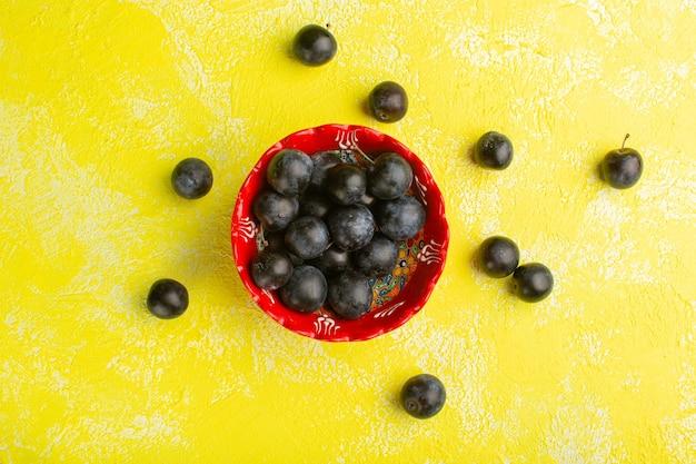 Vue de dessus du prunellier frais sur la surface jaune