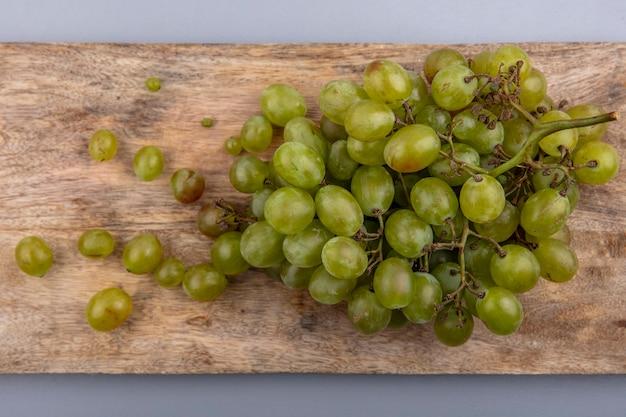 Vue de dessus du raisin blanc sur une planche à découper sur fond gris