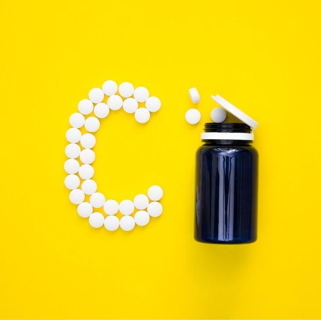 Vue de dessus du récipient en plastique et des pilules orthographe lettre
