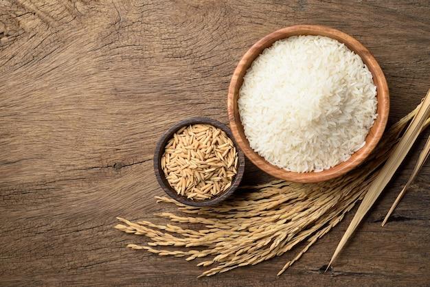 Vue de dessus du riz au jasmin blanc avec des oreilles de riz paddy sur fond de bois