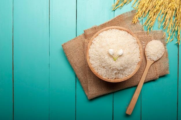 Vue de dessus du riz au jasmin avec une fleur de jasmin sur le dessus dans un bol en bois, une cuillère et une oreille de riz