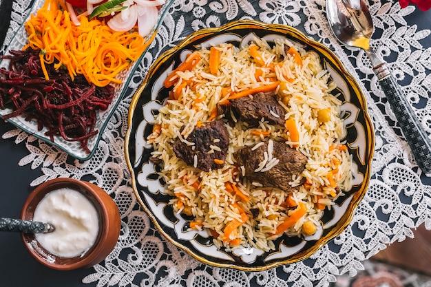 Vue de dessus du riz aux carottes cuit avec de l'agneau servi avec du yogourt et de la salade