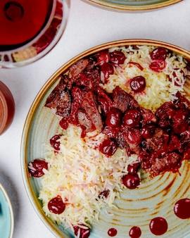 Vue de dessus du riz bouilli avec de la viande et des cerises