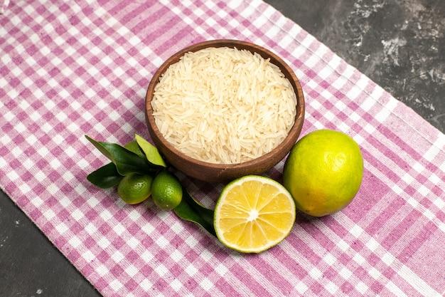 Vue de dessus du riz cru avec des citrons sur la couleur des fruits des aliments crus de surface sombre