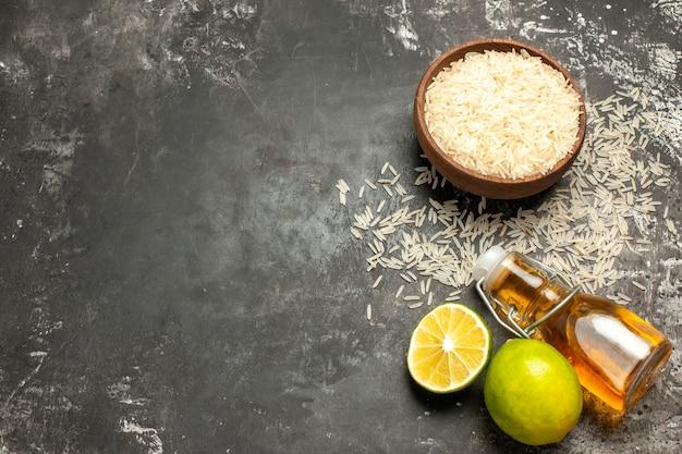 Vue de dessus du riz cru avec des citrons et de l'huile sur des fruits crus de surface sombre
