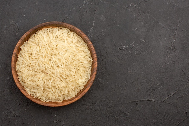 Vue de dessus du riz cru à l'intérieur de la plaque brune sur la surface grise