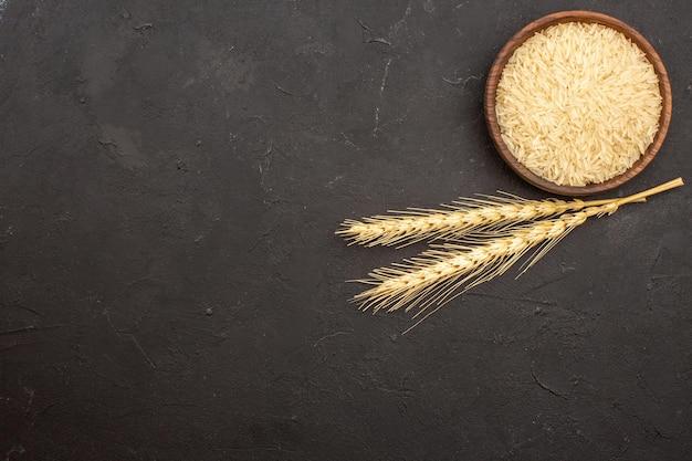 Vue de dessus du riz cru à l'intérieur de la plaque sur la surface grise
