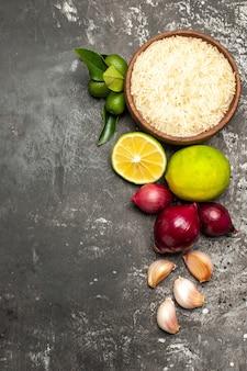 Vue de dessus du riz cru avec des oignons et de l'ail sur la salade mûre d'aliments crus de surface sombre
