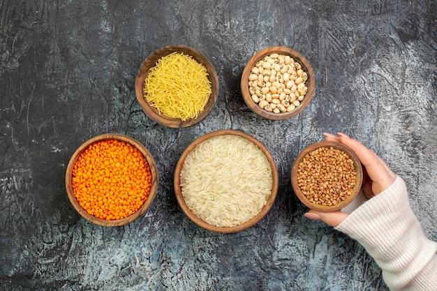 Vue de dessus du riz cru avec des vermicelles et du sarrasin cru à l'intérieur de petits pots sur la table gris clair