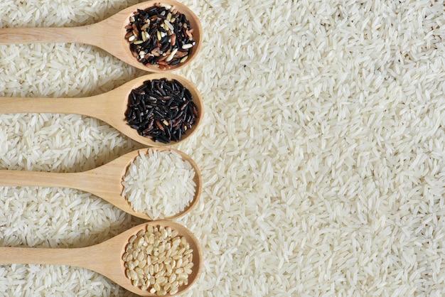 Vue de dessus du riz sur une cuillère en bois avec un fond de riz noir, divers riz bio sur la collection de cuillères en bois
