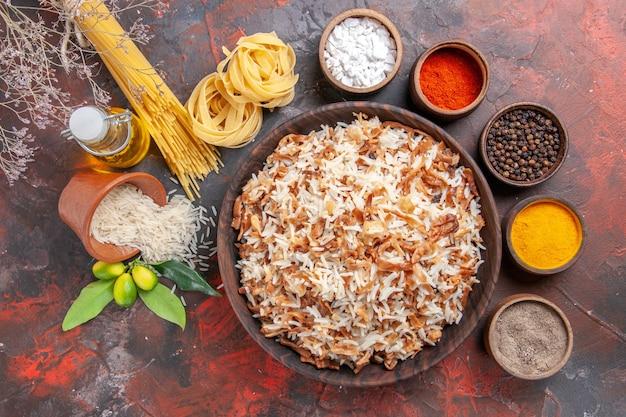 Vue de dessus du riz cuit avec des assaisonnements sur un plat de repas de surface sombre