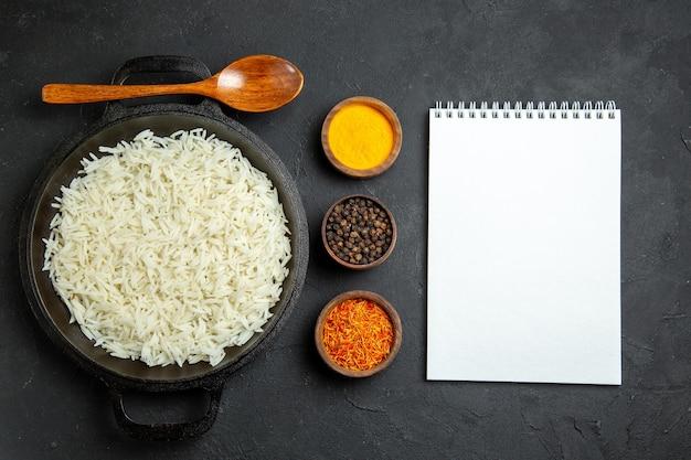 Vue de dessus du riz cuit à l'intérieur de la casserole avec des assaisonnements sur la surface sombre repas alimentaire riz dîner oriental