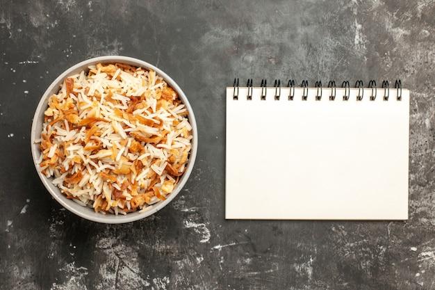 Vue de dessus du riz cuit à l'intérieur de la plaque sur le plat de surface sombre est repas repas sombre