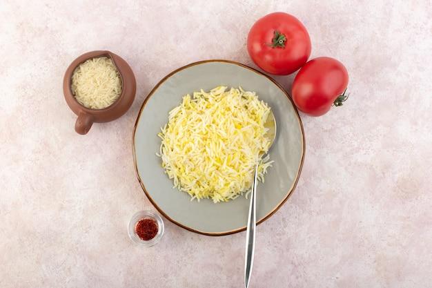 Une vue de dessus du riz cuit à l'intérieur de la plaque ronde avec des tomates rouges fraîches sur le bureau rose légume riz