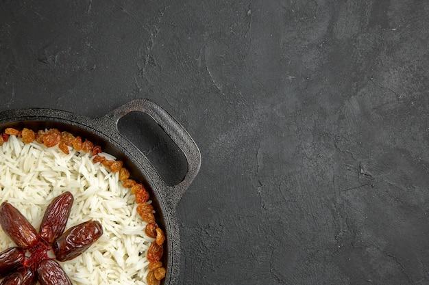 Vue de dessus du riz cuit avec des raisins secs à l'intérieur de la casserole sur une surface gris foncé repas alimentaire riz dîner oriental