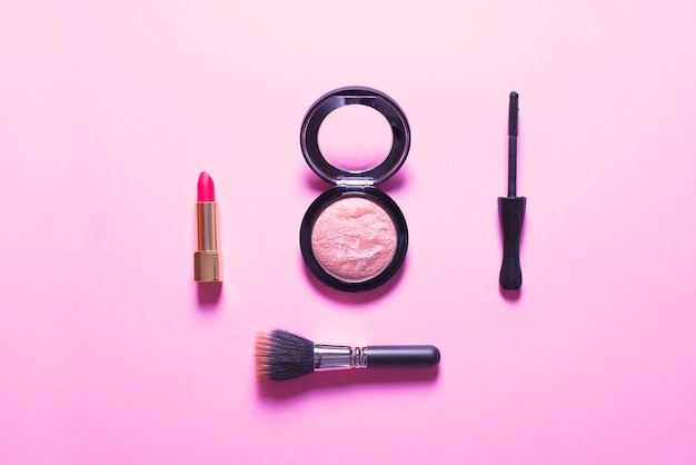 Vue de dessus du rouge à lèvres et du maquillage sur rose