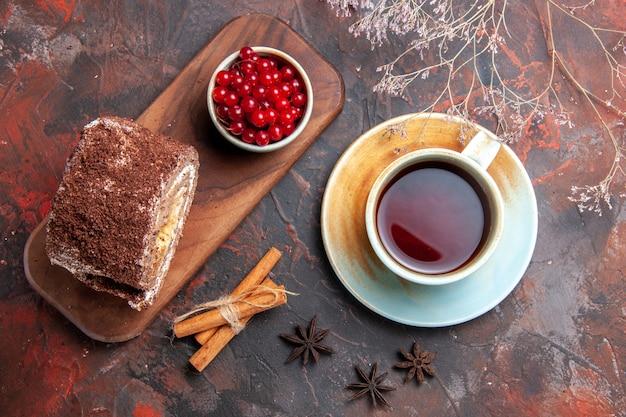 Vue de dessus du rouleau de biscuit avec du thé sur une surface sombre