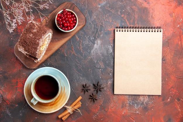 Vue de dessus du rouleau de biscuit avec une tasse de thé sur une surface sombre