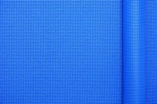 Vue de dessus du rouleau couleur bleu yoga fond de texture de tapis
