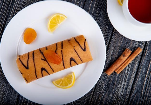 Vue de dessus du rouleau suisse avec de la confiture d'abricot sur une plaque blanche servie avec une tasse de thé sur rustique