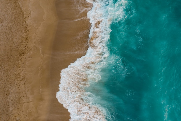 Vue de dessus du sable rencontre l'eau de mer