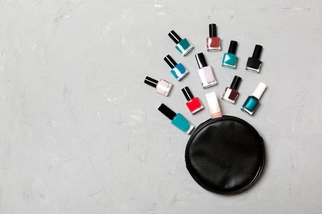 Vue de dessus du sac de cosmétiques avec vernis à ongles colorés tombés sur le ciment. beaux ongles