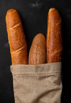 Vue de dessus du sac plein de pains baguette sur fond noir