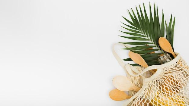 Vue de dessus du sac réutilisable avec des cuillères en bois et des feuilles