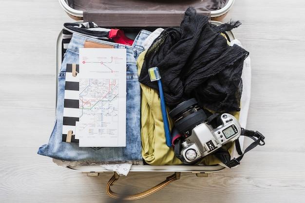 Vue de dessus du sac de voyage de la femme avec caméra, brosse et carte