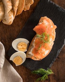 Vue de dessus du sandwich sur ardoise avec du saumon et des œufs durs