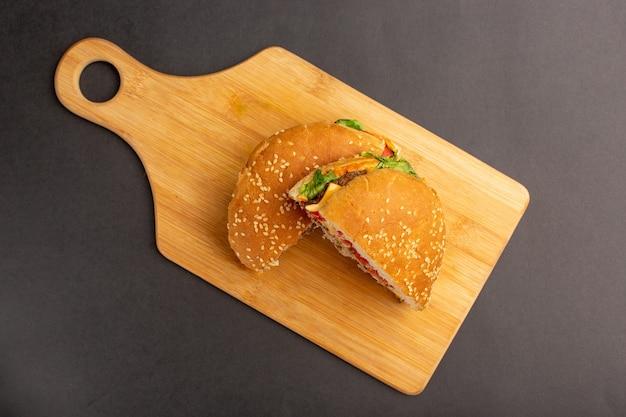 Vue de dessus du sandwich au poulet avec salade verte et légumes à moitié tranchés sur une surface en bois
