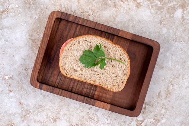 Vue de dessus du sandwich au salami fait maison sur une plaque en bois.
