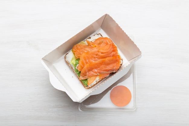 Vue de dessus du sandwich avec fromage à pâte molle et poisson rouge se trouve dans la boîte à lunch