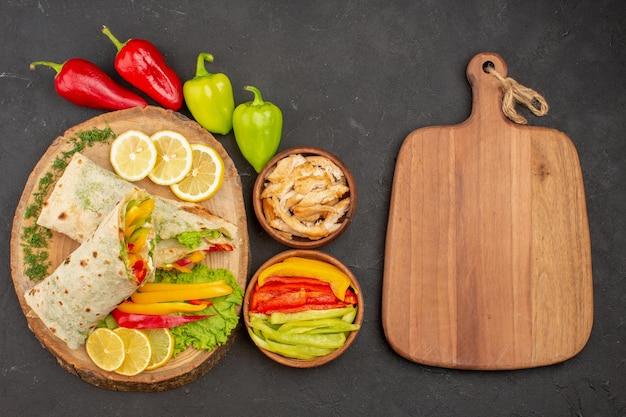 Vue de dessus du sandwich à la viande savoureuse shaurma en tranches avec des tranches de citron sur fond noir