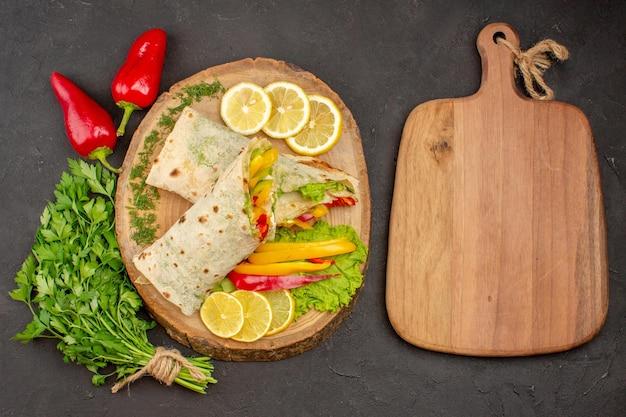 Vue de dessus du sandwich à la viande de shaurma en tranches avec des verts de citron sur fond noir