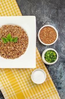 Vue de dessus du sarrasin cuit savoureux à l'intérieur d'une assiette blanche avec des verts sur une table gris clair