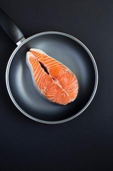 Vue de dessus du saumon de poisson cru dans une poêle à frire sur fond noir. fermer. emplacement vertical.