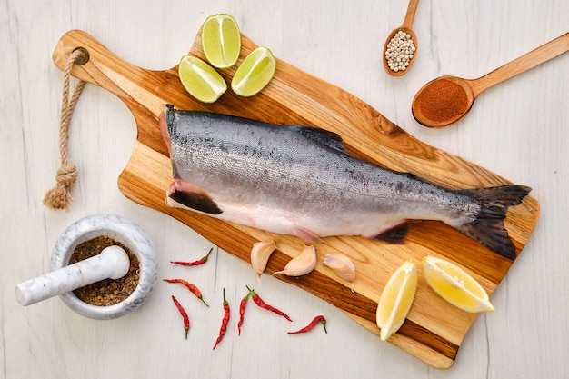 Vue de dessus du saumon rose sans tête frais cru sur une planche à découper en bois