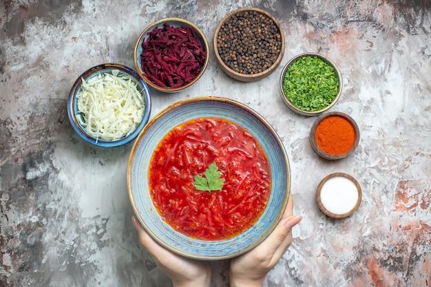 Vue de dessus du savoureux bortsch avec des assaisonnements et des légumes verts sur une surface blanche