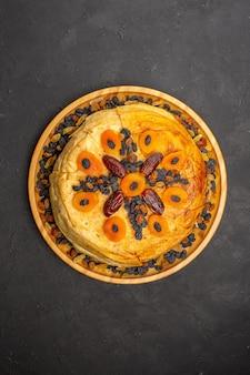 Vue de dessus du savoureux riz cuit shakh plov à l'intérieur d'une pâte ronde avec des raisins secs sur une surface grise