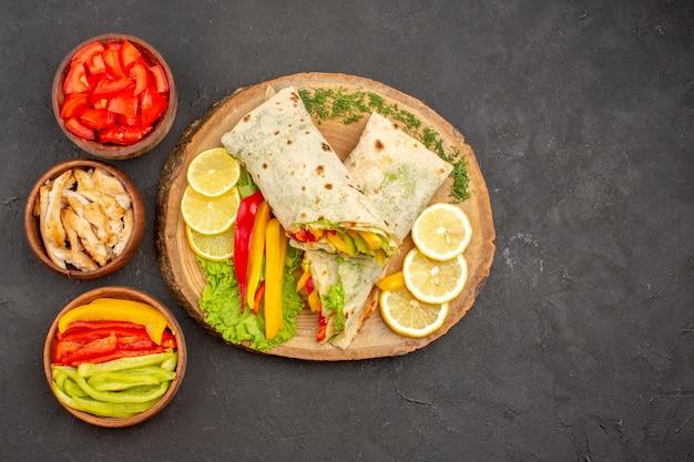 Vue de dessus du savoureux sandwich au poulet tranché shaurma avec des tranches de citron sur l'obscurité