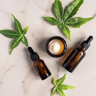 Vue de dessus du sérum pour le visage de cannabis et de la crème ou du concept de compte-gouttes d'huile.