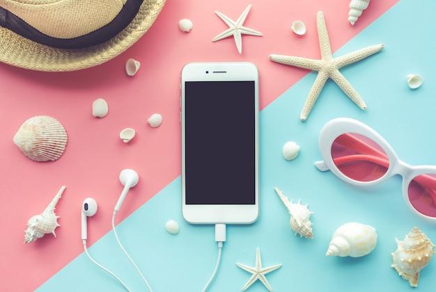 Vue de dessus du smartphone et élément de vacances sur fond de couleur.