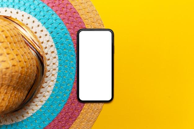 Vue de dessus du smartphone avec maquette près du chapeau d'été femme colorée