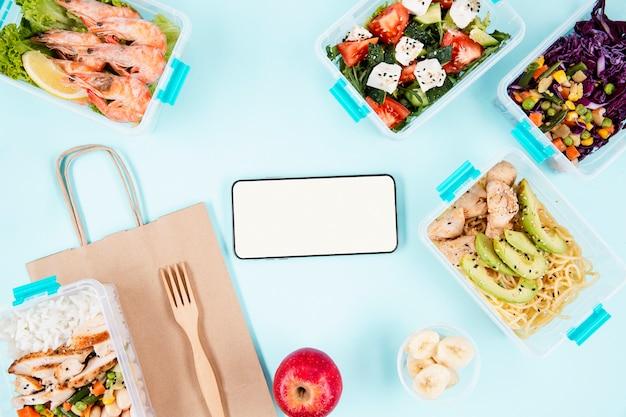 Vue de dessus du smartphone avec de la nourriture dans des casseroles