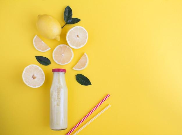 Vue de dessus du smoothie au citron dans une bouteille en verre sur fond jaune. espace de copie.