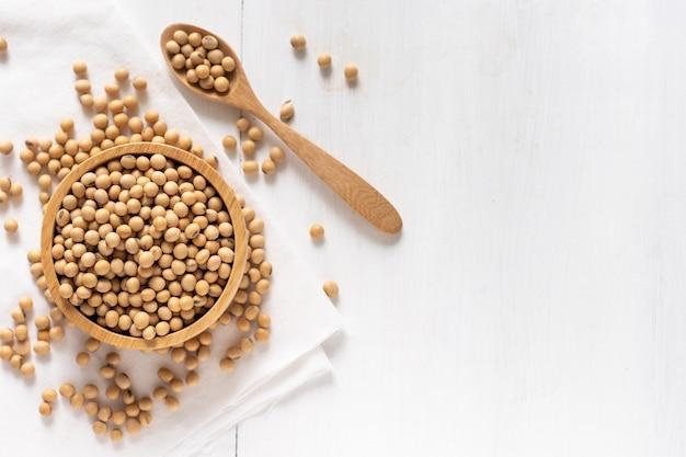Vue de dessus du soja ou du soja dans un bol sur fond de bois blanc