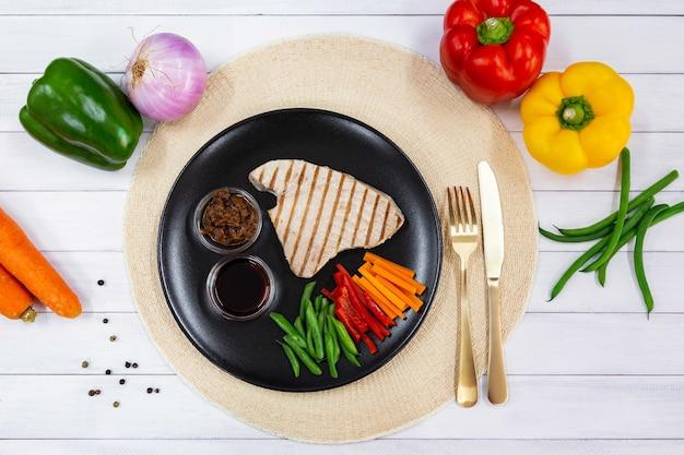 Vue de dessus du steak de thon grillé sur plaque noire avec sauce, oignon caramélisé et légumes frais